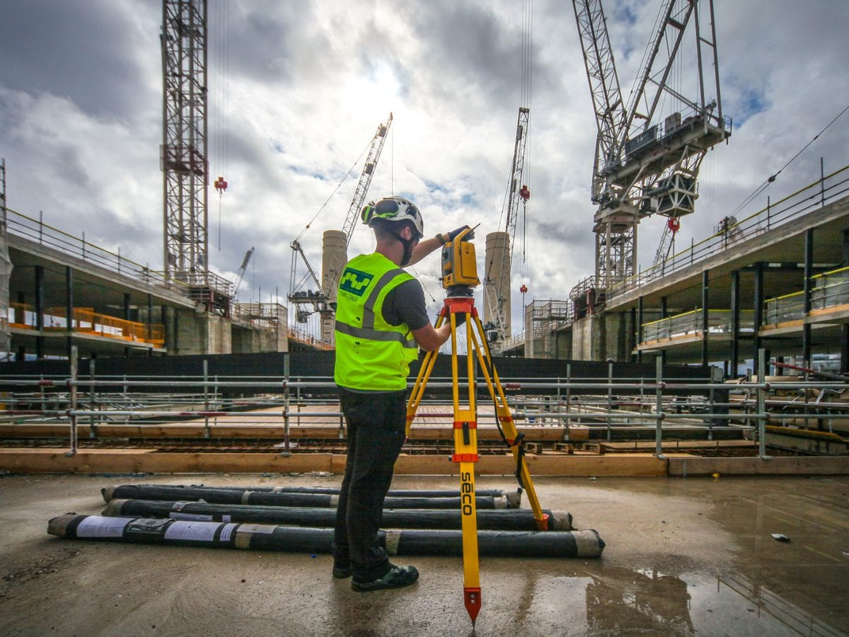 Surveyor using total station on construction site